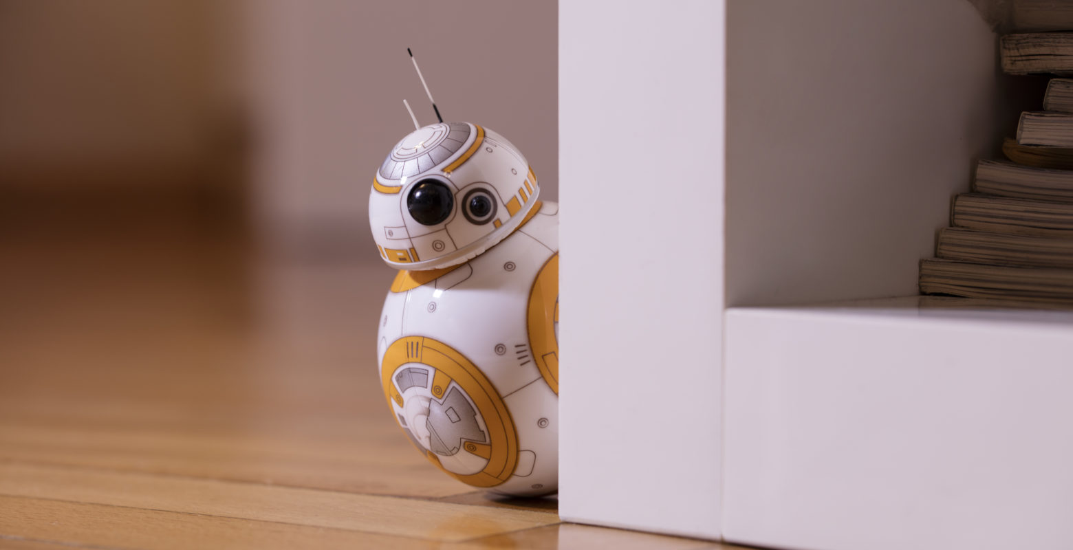 ?stanbul, Turkey - December 12, 2015: Portrait of BB-8 toy hiding behind a bookshelf. New droid of Star Wars movie appearing in The Force Awakens episode. BB-8 toy is produced by Sphero for Lucas Film.